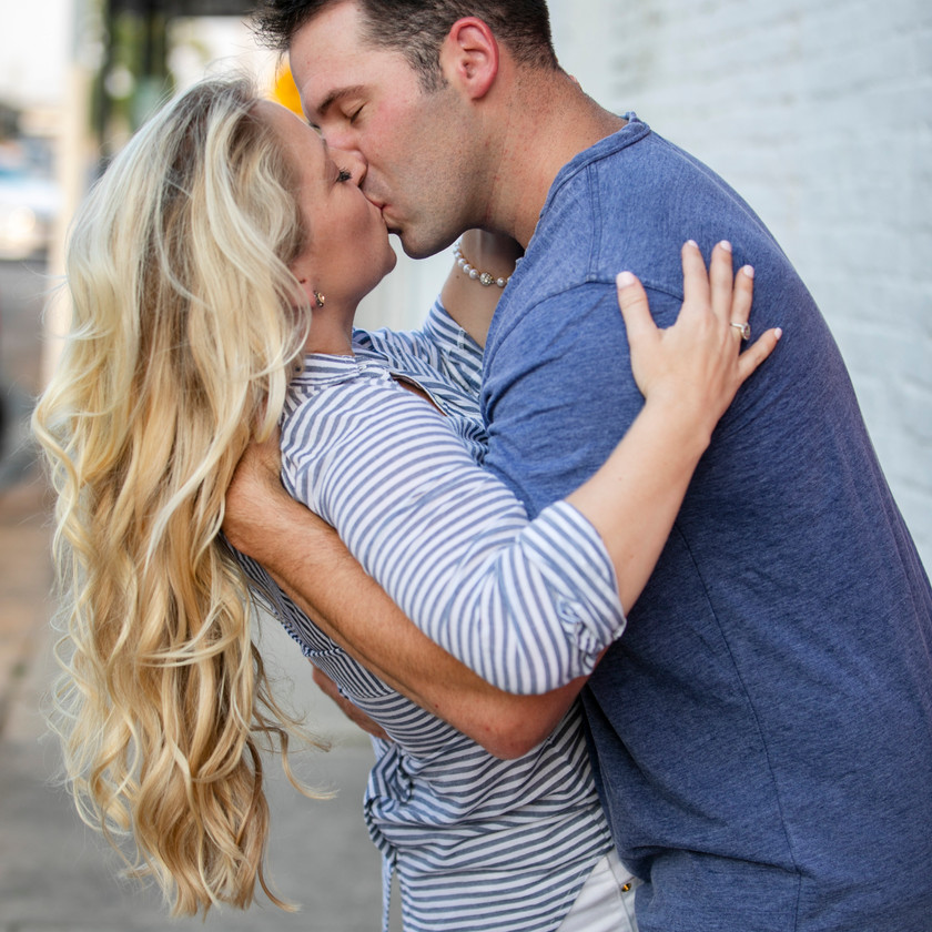 man and woman kissing in engagement photoshoot photo
