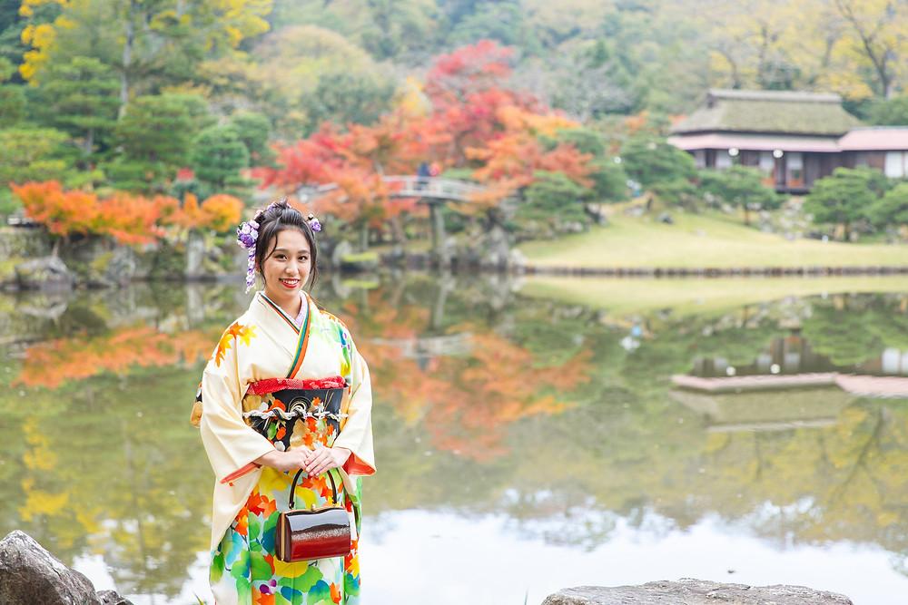 滋賀県彦根市の玄宮園で、彦根城を背景に成人式の前撮り撮影を女性カメラマンが写真撮影しました。