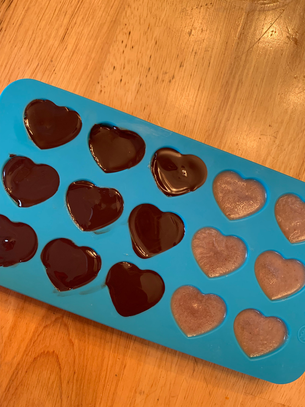Heart-shaped silicone mold filled with a strawberry, coconut butter, and cashew butter mixture and half of the hearts topped with dark chocolate