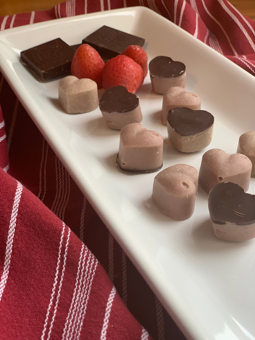 Valentine Fat Bombs on a long, white platter with strawberries and dark chocolate squares