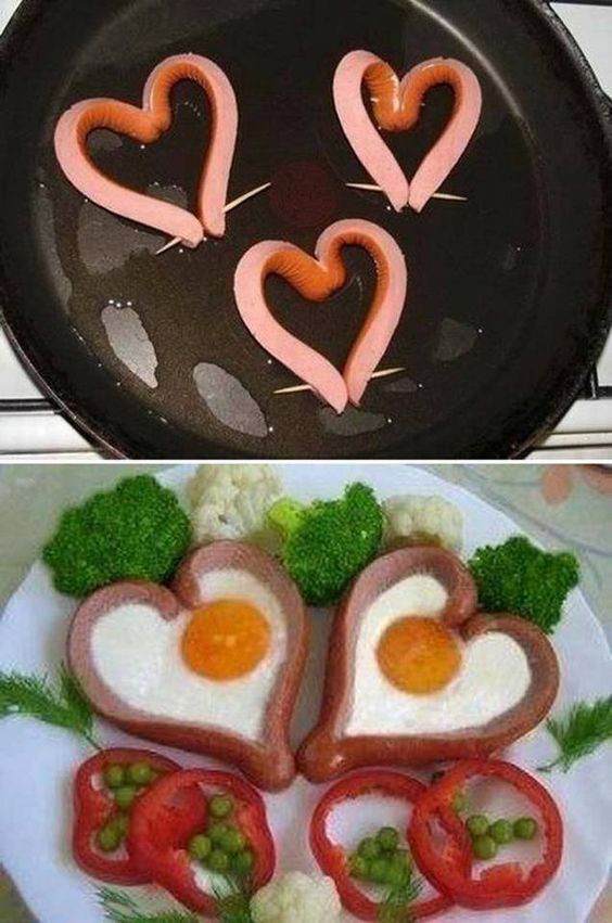 Sunny-side eggs inside a sausage that has been split down the middle 90% of the way and inverted to make a heart shape and held together with a toothpick