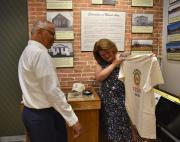 Lieutenant Governor Rutherford being presented with a historical society t-shirt, hat and ornament.