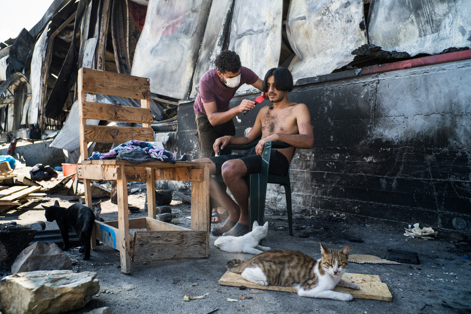 Mustafa, a Moroccan, cuts the hair of a migrant from Iraq in a kind of home barber shop in the vicinity of what was the old food market.