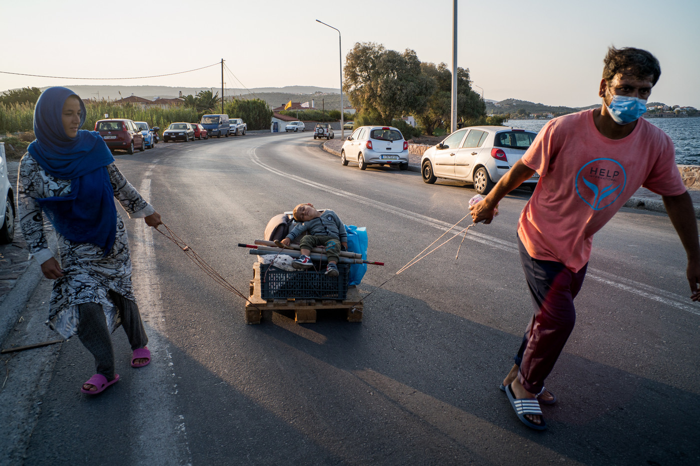 Moha, born in Turkey, is carried by his parents on the way to Kara-tepe.  Hundreds of families made homemade wagons with all kinds of material that remained without being destroyed from fire.