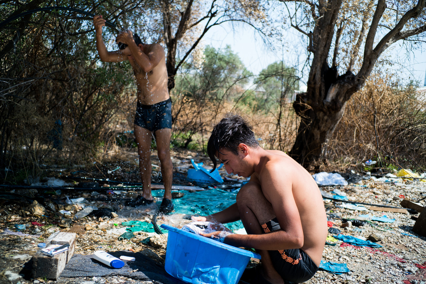 Refugees take a shower and wash their clothes on a makeshift space on the side of the road. After moving to the new camp, people were forced to carry out this type of action outside due to lack of water, toilets and electricity.