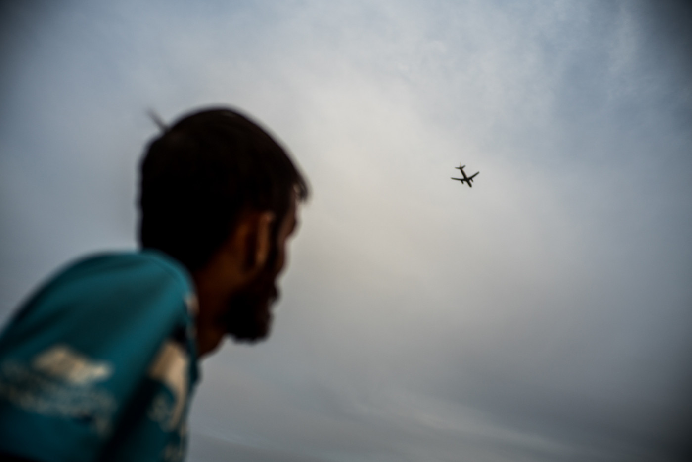 An Afghan refugee watches the passage of a plane on the shores of the sea that connects the Turkish coast with the island of Lesbos.