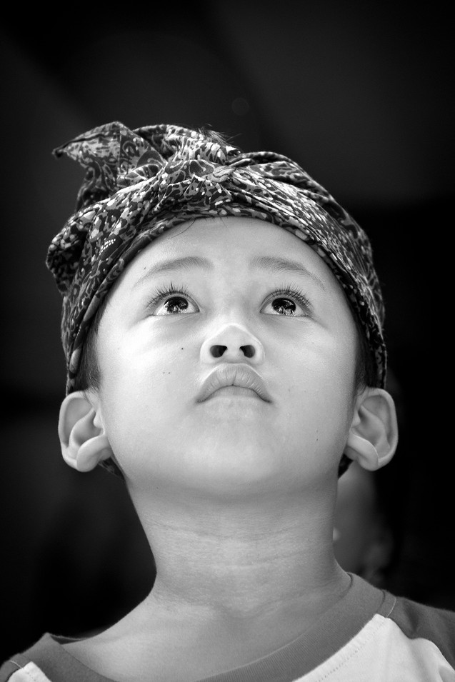 Balinese child looks stunned at the cremation of the body while next to him the women sing