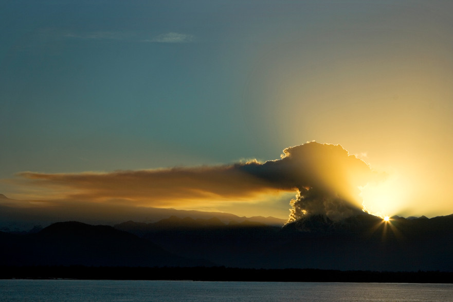 The rays of dawn draw the silhouette of the fumarole of the Chaitén volcano from the boat that travels towards Puerto Montt.