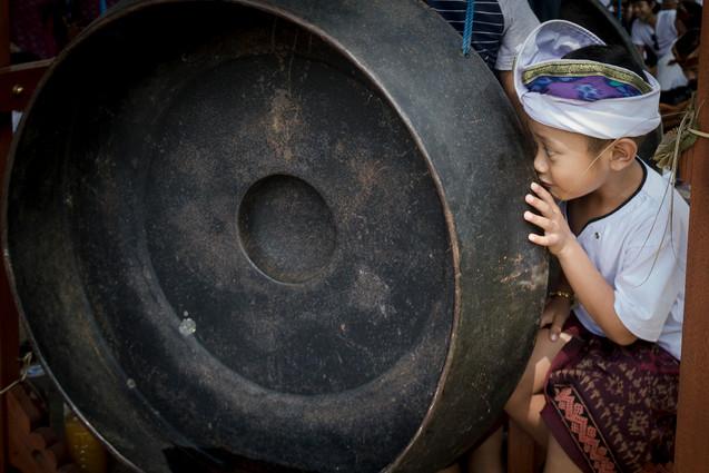 Balinese boy hiding behind a gong