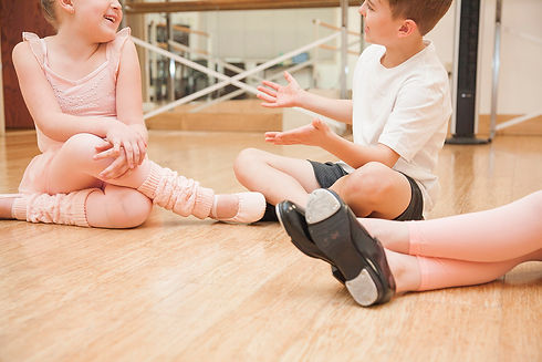 Children talking in dance studio with tap and ballet shoes