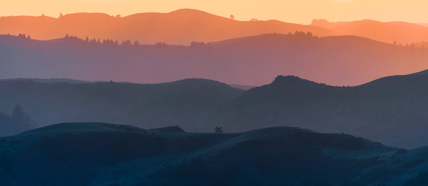 Sunset view of hills and valleys, each l