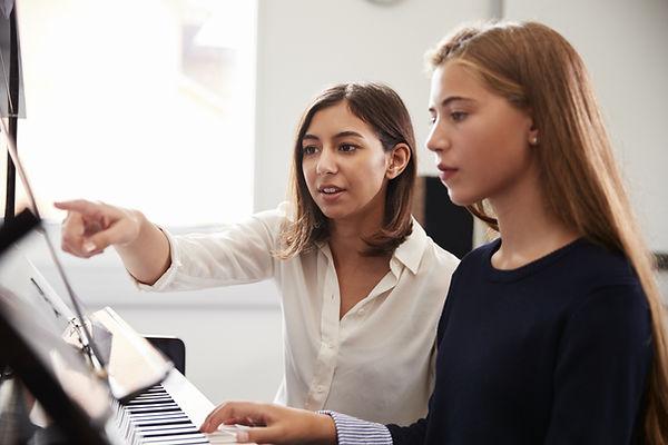 Lærer og elev ved klaver lektion