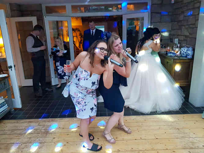 Two Ladies Singing Karaoke at a Christening Party at As You Like It in Jesmond. Booked with a DJ Disco Package and Some Kids Games