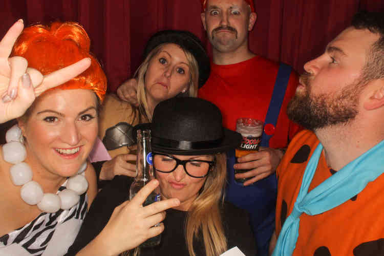 Booked Photo Booth Hire at a Fancy Dress Party in Carlisle. Friends wearing sill props and having their pictures taken with a DJ.