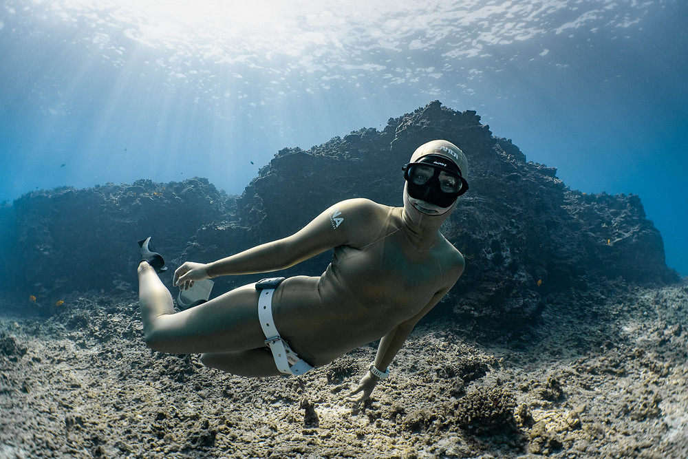 Kona Freediver wearing a custom suit with weight belt and freediving fins