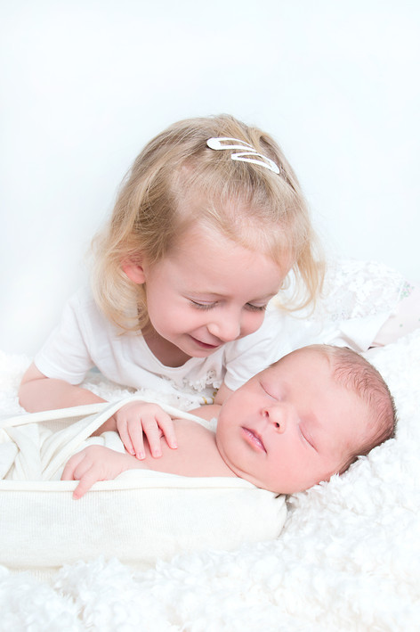Big sister proudly holds her baby sister
