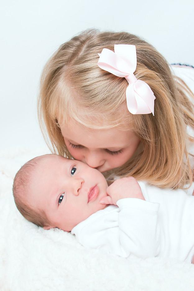 Big sister kisses baby brother
