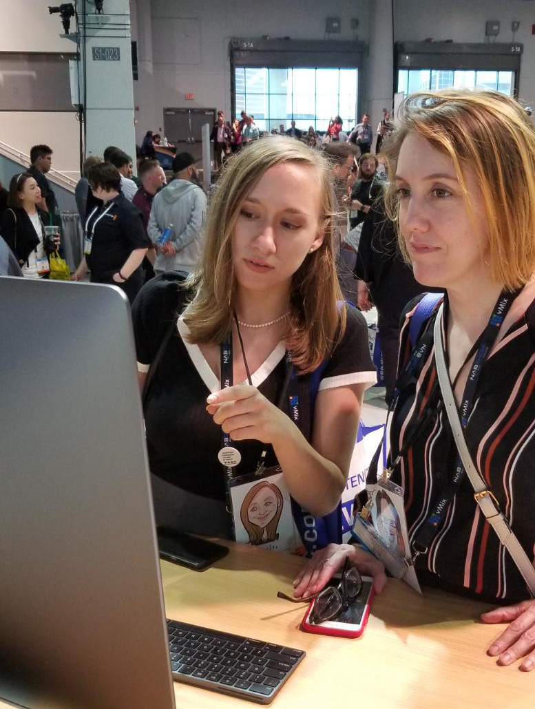 Grace Novak and Kirsten McNary look interested at a computer screen.