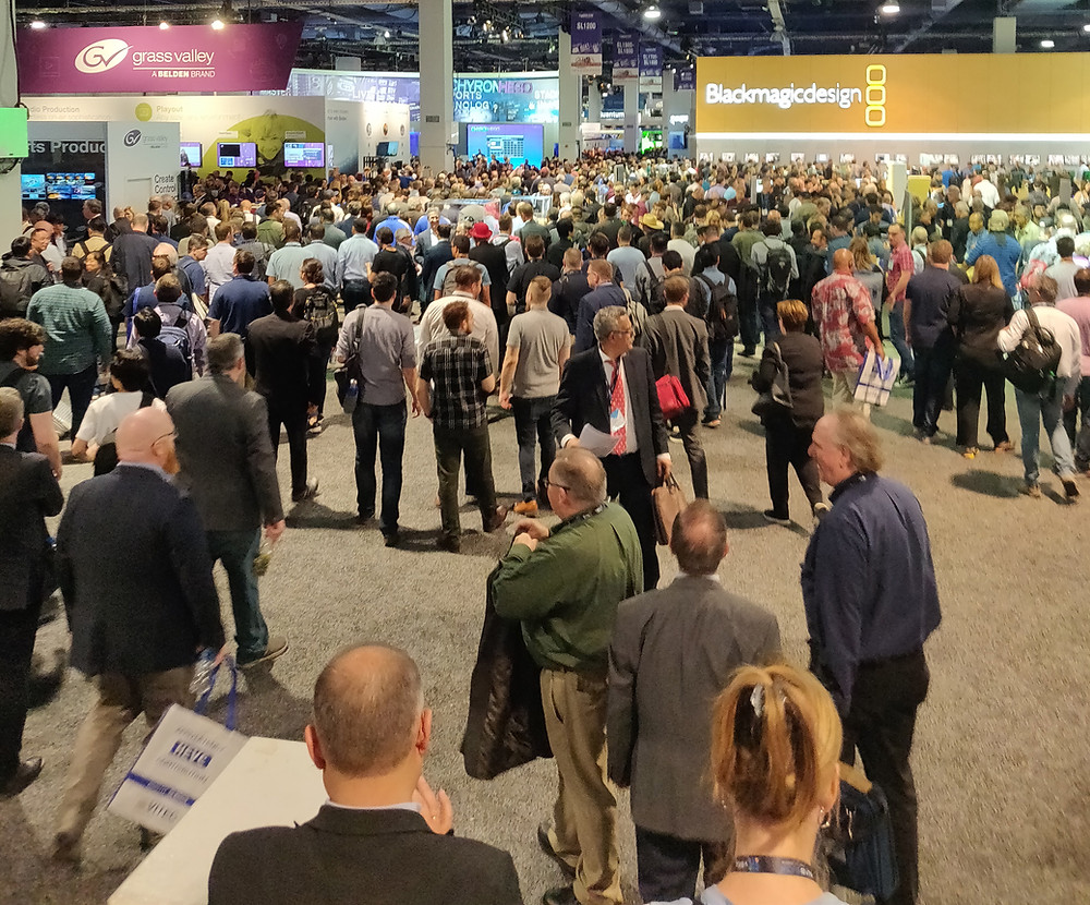 A large crowd of people at the NAB show floor at the South Hall in front of the BlackMagic booth.