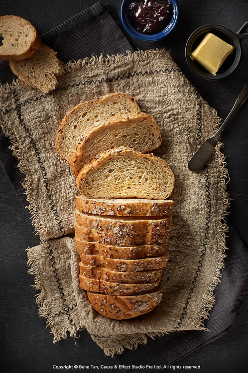Wholegrain Bread Loaf with butter and jam flat lay on dark background