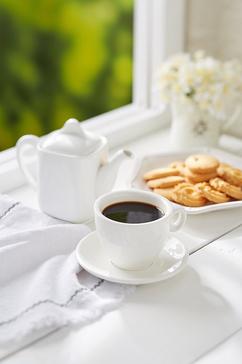 Black Coffee with assorted biscuits on white rustic wooden top