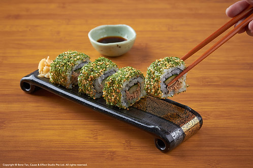 Picking up a Seaweed Maki Roll with chopstick on a Japanese bamboo background