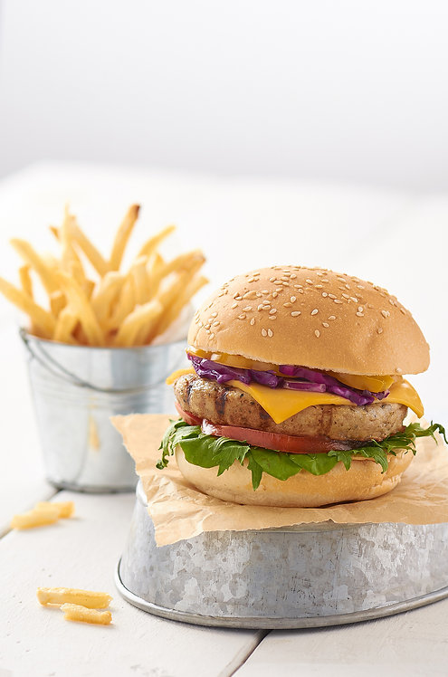 Grilled Chicken Burger with Cheese and Baked Fries on white wooden top