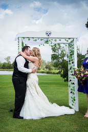Wedding kiss infront of arch