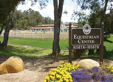 front of fairbanks ranch equestrian center, enterance sign, riding arena one, three arenas, dressage and jumping, green grass for grazing