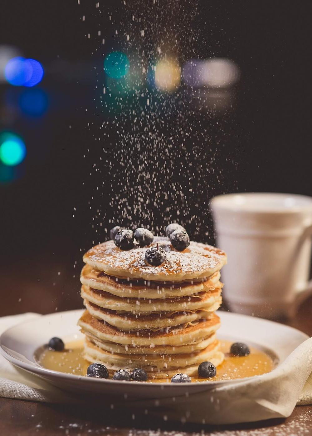 Pile de pancakes, myrtilles et sucre glace