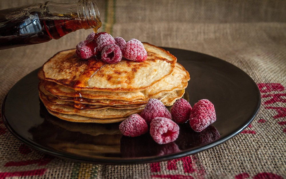Pile de pancakes, framboises et sirop d'érable