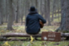 Man Playing Guitar in a Forest