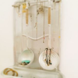 An old french kitchen utensils wall mount repurposed as a jewlery hanger.