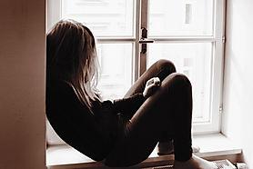 Trauriges Mädchen am Fenster