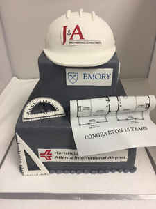Corporate construction cake with edible images logos .  Edible architecture tools, hard hat and logos.  At this time, this cake is not available for Online Ordering.  Please fill out our Quote Request form below to obtain pricing for this cake.