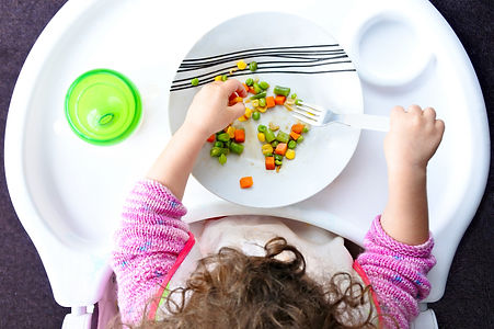Above view of a little toddler child eats vegetables. Childhood and children health care c