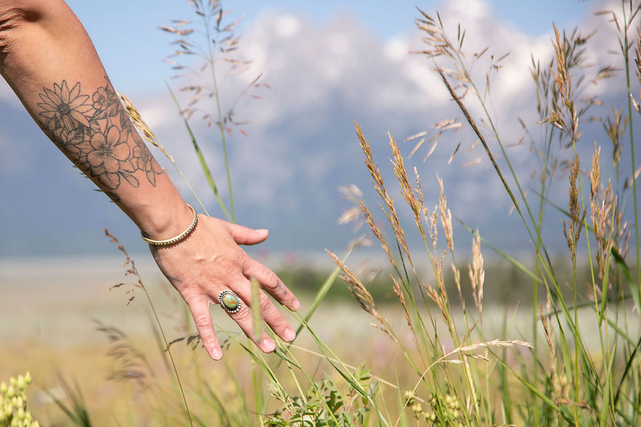 Photo of Annelies' hand in tall grass with mountains in the background