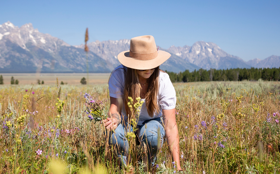 Photo Annelies picking wildflowers in a meadow in the Tetons