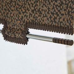 Brown textured castle design with decorative pole roller blind
