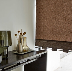 Brown roller blinds with a castille scallop, dark brown braiding and a decorative pole