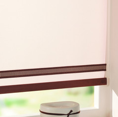 Cream roller blind with a brown braiding