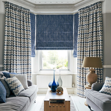 Blue and yellow striped curtains with a roman blind