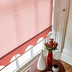 Pink roller blinds with a colonnade scallop, braiding and decorative pole
