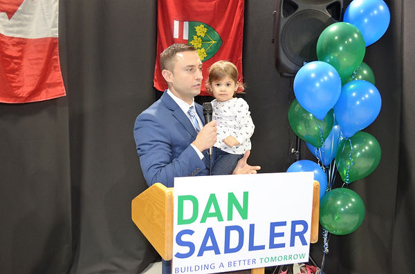 Dan Sadler speaking behind a podium, speaking into a microphone and holding a small child