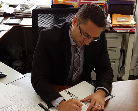 Dan Sadler writing at a desk