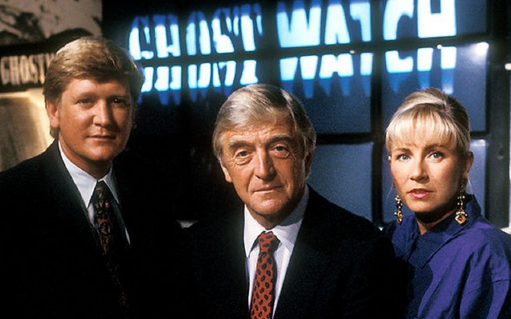 Film still from Ghostwatch. Two men and a woman. The men wear suit and tie, while the woman wears a purple blouse and earrings. Behind them a row of televisions spell out Ghostwatch.