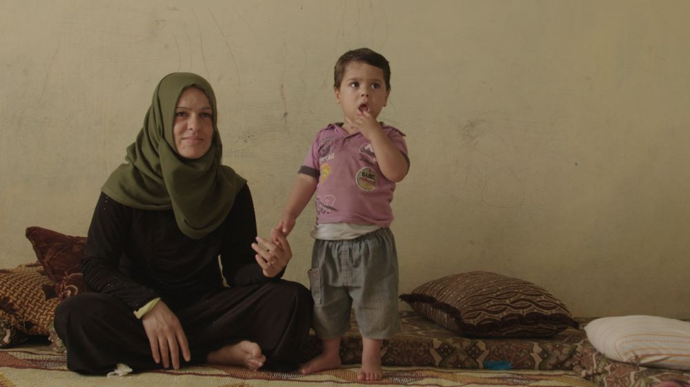 A Syrian mother sits on the ground and holds the hand of her young child who stands with a finger in his mouth