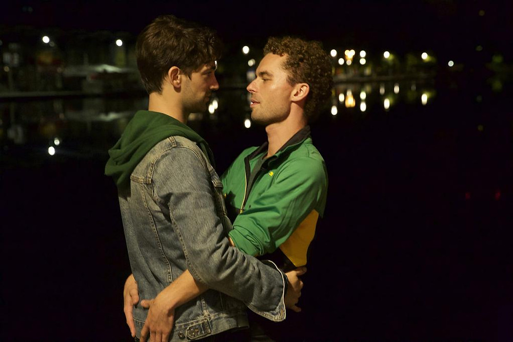 Two men hold each other at nighttime and look into each others' eyes.