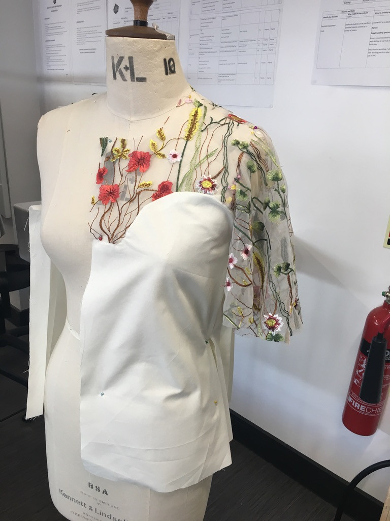 A manikin with the beginning parts of a garment in production. There is a sheer floral material  draped over the chest and shoulder, which is attached to a white piece of material.