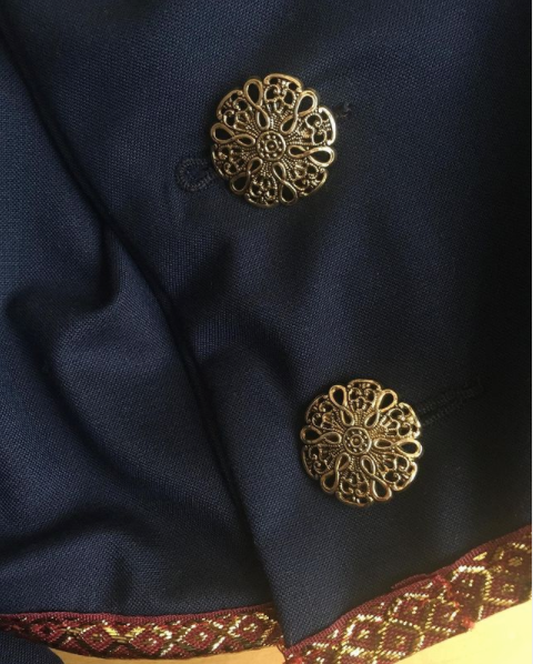 A blue jacket with gold intricate buttons and a red and gold hem